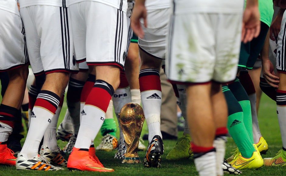 Germany's players dance around the trophy after the World Cup final soccer match between Germany and Argentina at the Maracana Stadium in Rio de Janeiro, Brazil, Sunday, July 13, 2014. Germany beat Argentina 1-0 to win its fourth World Cup title. AP