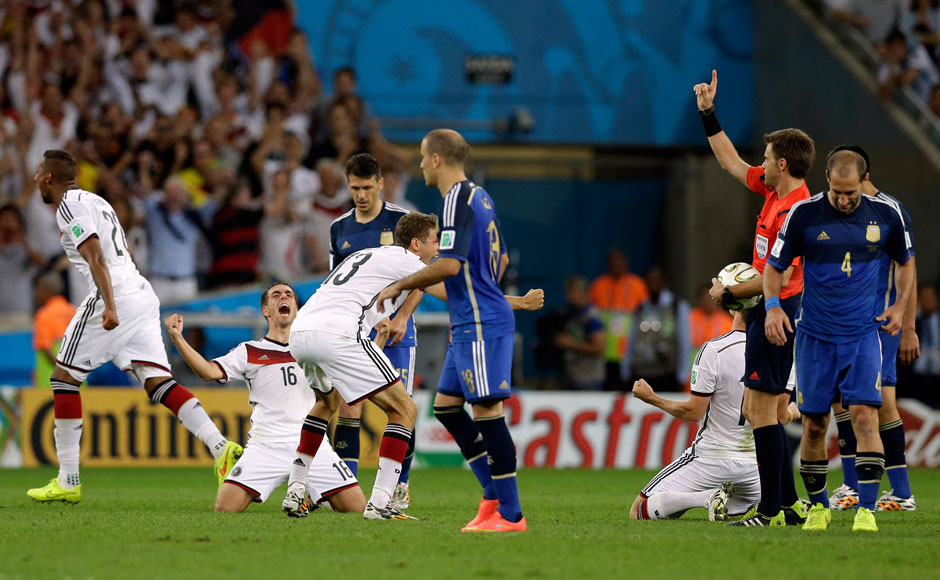 Germany's team captain Philipp Lahm, second left, celebrates as referee Nicola Rizzoli from Italy blows the final whistle during the World Cup final soccer match between Germany and Argentina at the Maracana Stadium in Rio de Janeiro, Brazil, Sunday, July 13, 2014. Germany beat Argentina 1-0 to win its fourth World Cup title. AP