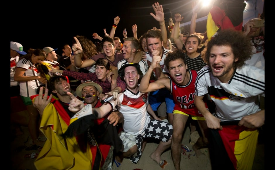 Soccer fans of the Germany national soccer team celebrate thier team's victory during a live broadcast of the final World Cup match between Germany and Argentina, inside the FIFA Fan Fest area on Copacabana beach, Rio de Janeiro, Brazil, Sunday, July 13, 2014. Mario Goetze volleyed in the winning goal in extra time to give Germany its fourth World Cup title with a 1-0 victory over Argentina. (AP Photo/Silvia Izquierdo)