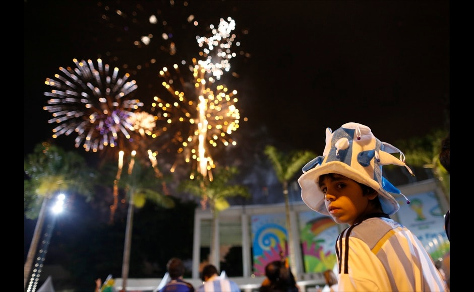An young Argentina soccer fan stands outside the Maracana stadium during the fireworks display, after the World Cup final match between Argentina and Germany in Rio de Janeiro, Brazil, Sunday, July 13, 2014. Mario Goetze volleyed in the winning goal in extra time to give Germany its fourth World Cup title with a 1-0 victory over Argentina. (AP Photo/Leo Correa)
