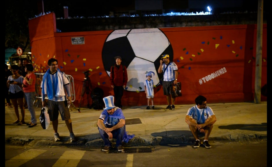 Argentina soccer fans stay on a sidewalk after Argentina was defeated by Germany during the final match of the World Cup outside the Maracana stadium in Rio de Janeiro, Brazil, Sunday, July 13, 2014. Mario Goetze volleyed in the winning goal in extra time to give Germany its fourth World Cup title with a 1-0 victory over Argentina. (AP Photo/Manu Fernandez)