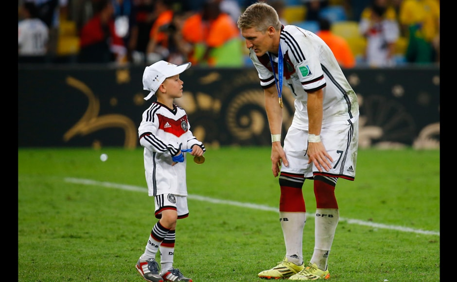 The bloodied and bruised Bastian Schweinsteiger (R) having a lovely moment with Louis Gabriel Podolski, the son of his teammate Lukas Podolski. Reuters