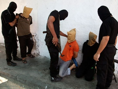 Hamas militants grab Palestinians suspected of collaborating with Israel, before executing them in Gaza City. Reuters image