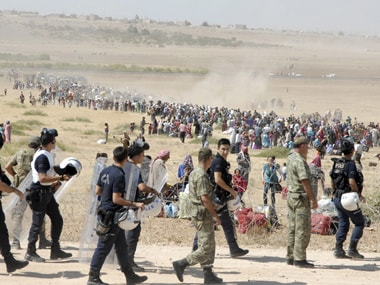 Turkish policemen and soldiers walk as Syrian Kurds wait behind the border fence to cross into Turkey. Reuters image