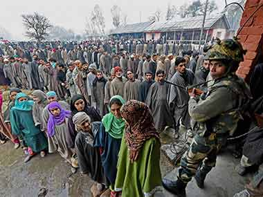 Jammu and Kashmir residents gather to vote outside a polling booth, while a security official stands on guard. PTI