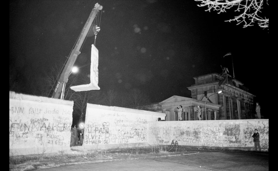 The first section of the Berlin Wall to be dismantled by East Germany is lifted by a crane near the Brandenburg Gate in East Berlin