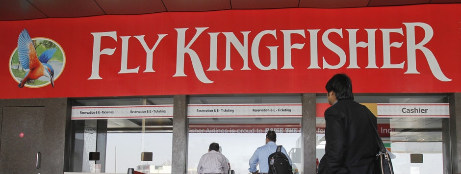 Customers stand at a Kingfisher Airlines reservation office at the domestic airport in Mumbai