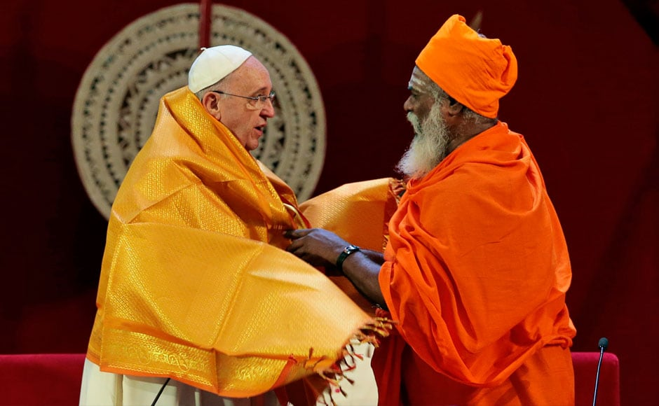 Sri Lankan Hindu priest Kurakkal Somasundaram, right, presents a shawl to Pope Francis during an inter-religious meeting in Colombo, Sri Lanka. Pope Francis has worked to avoid cloaking himself in the mystical power that popes are so often endowed with by believers, but still many of the thousands who came out to see him hoped for a touch or a blessing from him. AP