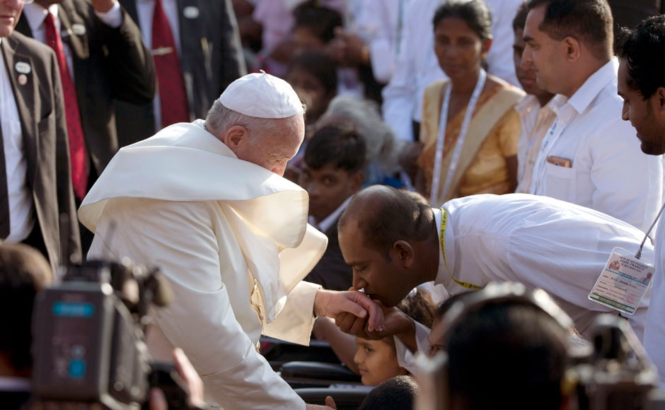 A man kisses Pope Francis's hand upon his arrival in the seafront Galle Face Green for the canonization ceremony of Joseph Vaz, in Colombo, Sri Lanka, Wednesday, Jan. 14, 2015.  Pope Francis pressed his call for Sri Lankan unity and reconciliation Wednesday with a Mass in Colombo to canonize the country's first saint and a visit to the war-ravaged north to pray at a shrine revered by both Sinhalese and Tamil faithful. AP