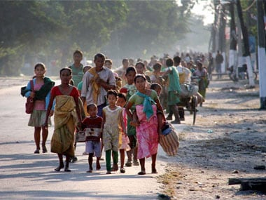 Bodo villagers moving towards a safer place after they were attacked by Adivashis, in Kokrajhar. PTI