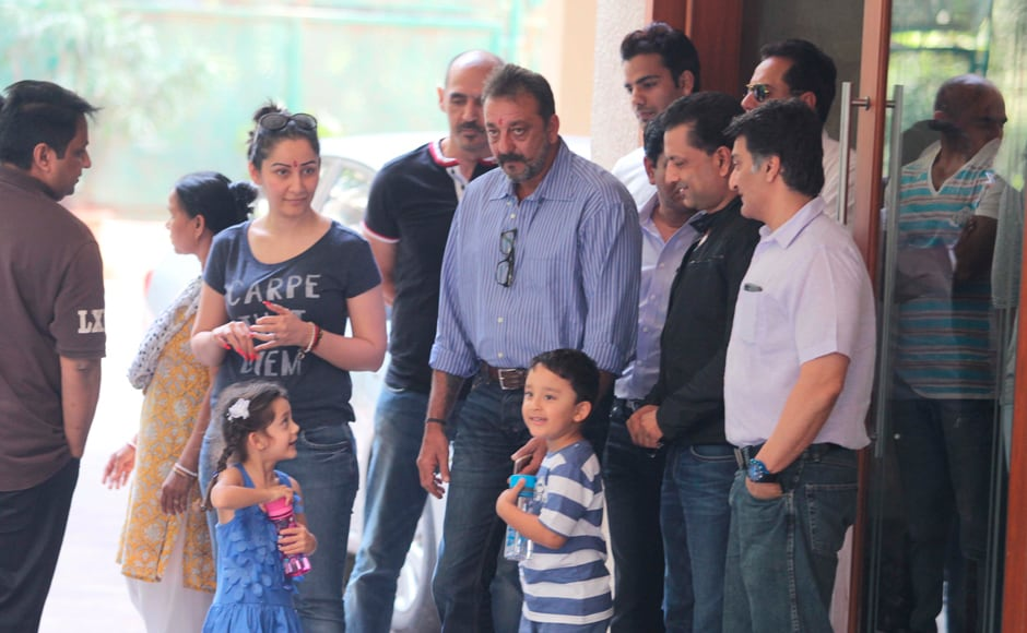 Sanjay Dutt's twins look quite cheerful, clutching what look like brand new water bottles, as the actor walks out of his home, flanked by family and friends: Firstpost