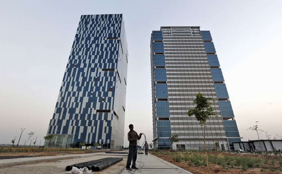 """A worker folds the cable of a welding machine in front of two office buildings at the Gujarat International Finance Tec-City (GIFT) at Gandhinagar, in the western Indian state of Gujarat, April 10, 2015. India's push to accommodate a booming urban population and attract investment rests in large part with dozens of """"smart"""" cities like the one being built on the dusty banks of the Sabarmati river in western India. Picture taken April 10, 2015.  REUTERS"""