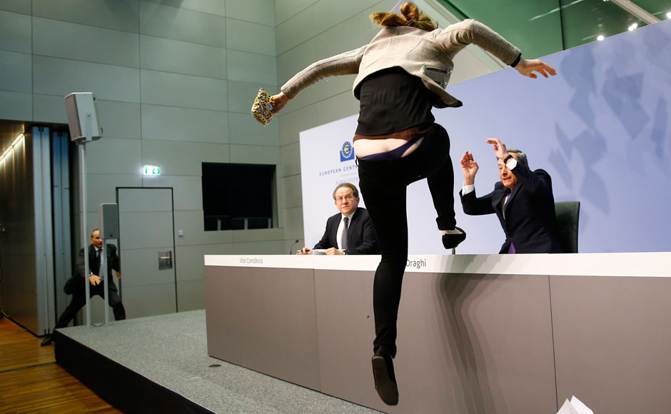 A protester jumps on the table in front of the European Central Bank President Mario Draghi during a news conference in Frankfurt, April 15, 2015. The news conference was disrupted on Wednesday when a woman in a black T-shirt jumped on the podium. REUTERS
