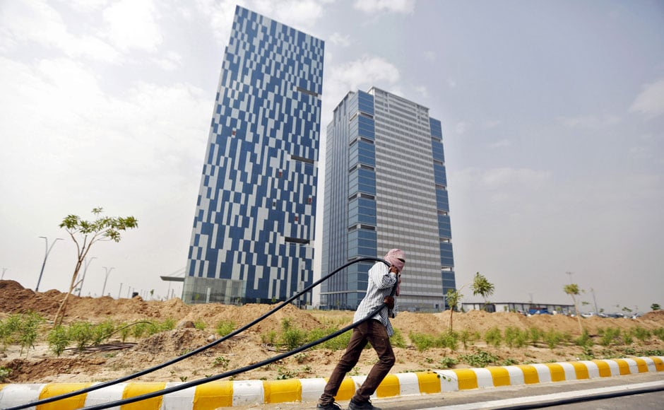 """A labourer pulls a cable in front of two office buildings in Gujarat International Finance Tec-City (GIFT) at Gandhinagar, in the western Indian state of Gujarat, April 10, 2015. India's push to accommodate a booming urban population and attract investment rests in large part with dozens of """"smart"""" cities like the one being built on the dusty banks of the Sabarmati river in western India. Picture taken April 10, 2015.  REUTERS"""