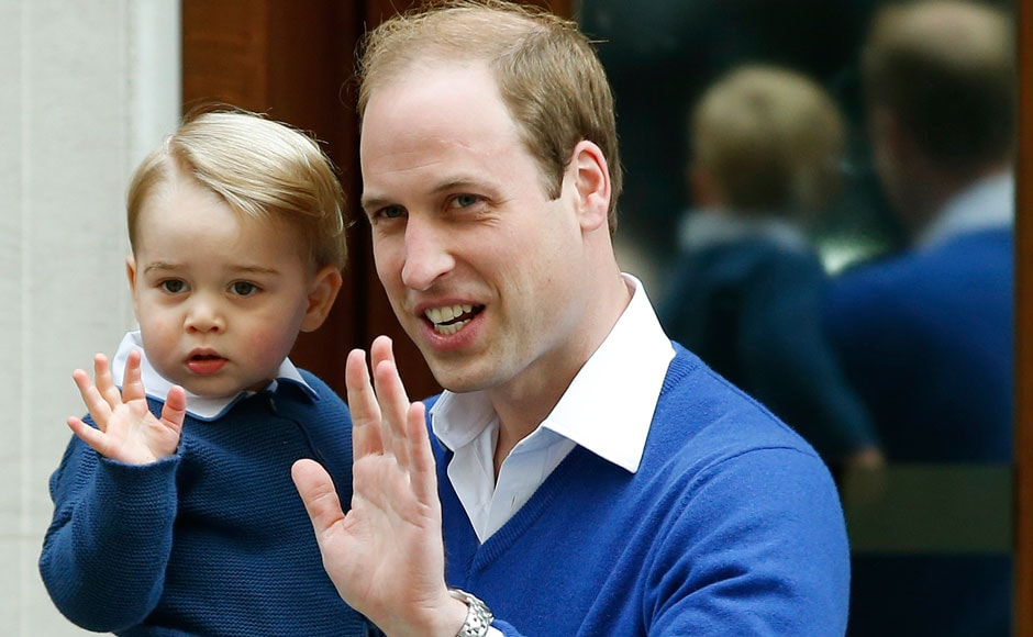 Britain's Prince William and his son Prince George wave as they return to St. Mary's Hospital's exclusive Lindo Wing, London, Saturday, May 2, 2015. William's wife, Kate, the Duchess of Cambridge, gave birth to a baby girl on Saturday morning. AP