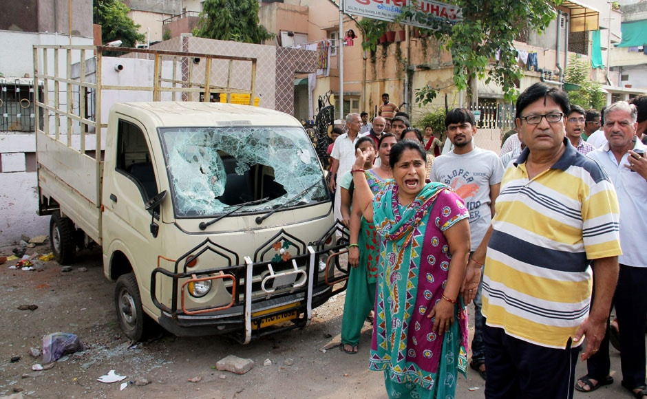 Ahmedabad: People stand in front of a damaged vehicle after violent clashes between Patel community and OBC members at Juna Wadaj locality in Ahmedabad on Tuesday. PTI
