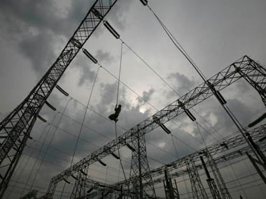 Worker installs electric power cable at a newly constructed power station in Jammu