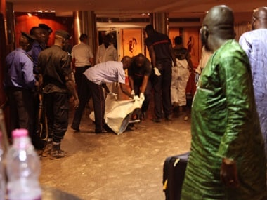 Mali security personal cover the body of a victim inside the Radisson Blu hotel after an attack by gunmen on the hotel in Bamako. AP