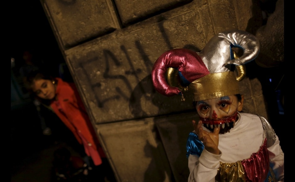 A child dressed up as a dead harlequin gestures during a Catrinas parade in Mexico City