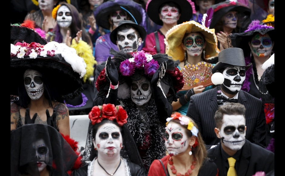 people with their faces painted to look like the popular mexican figure called catrina