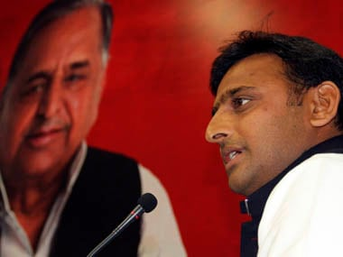 Akhilesh Yadav speaks in front of a portrait of his father and Samajwadi Party President Mulayam during a meeting with the newly elected legislators at party headquarters in Lucknow