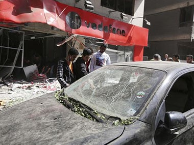 People look at a damaged vehicle outside a Vodafone branch following a blast, in Cairo