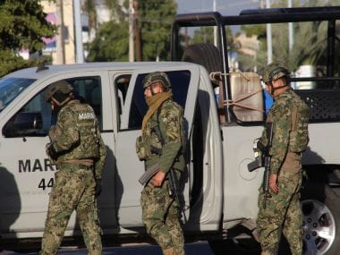 """Mexican Navy marines stand next to their vehicle after they participated in the recapture of Mexico's most wanted drug lord, Joaquin """"El Chapo"""" Guzman. AP"""