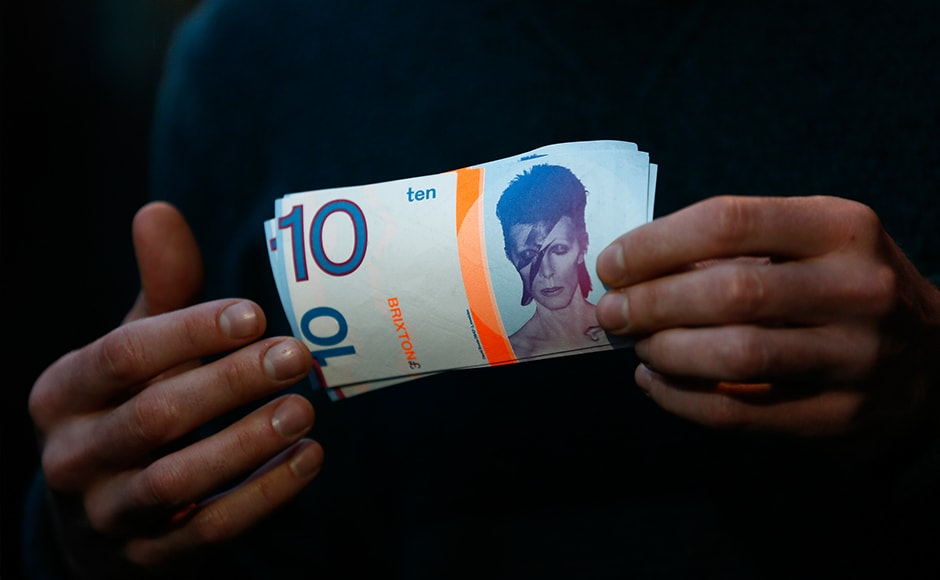 """A man holds a 10 Brixton Pounds note, which is adorned with an image of Brixton native David Bowie in Brixton, south London, January 11, 2016. David Bowie, a music legend who used daringly androgynous displays of sexuality and glittering costumes to frame legendary rock hits """"Ziggy Stardust"""" and """"Space Oddity"""", has died of cancer. The Brixton Pound is an alternative currency which can be used in businesses in the south London neighbourhood. REUTERS/Stefan Wermuth"""
