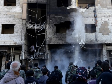 Syrian pro-government forces inspect the damage following suicide bombings. AFP