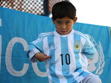 Five-year-old Afghan boy Murtaza Ahmadi posing with a jersey sent to him by Argentine football star Lionel Messi. AFP