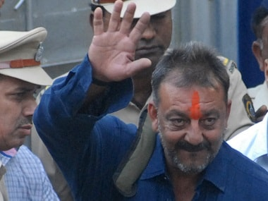 Sanjay Dutt waves as he is escorted by officials from Yerwada Jail. AFP