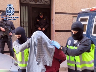 Masked police officers take one of the arrested persons at an undisclosed location. AFP / Policia Nacional
