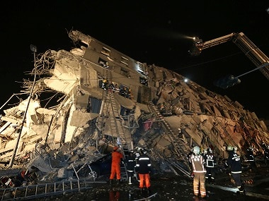 Rescue workers search a toppled building after an earthquake in Tainan, Taiwan on Saturday. AP