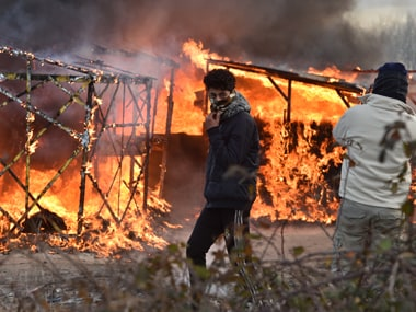 """A migrant walks past shacks burning during the dismantling of half of the """"Jungle"""" migrant camp in the French northern port city of Calais, on February 29, 2016. Clashes broke out between French riot police and migrants on February 29 as bulldozers moved into the grim shantytown on the edge of Calais known as the """"Jungle"""" to start destroying hundreds of makeshift shelters. AFP"""