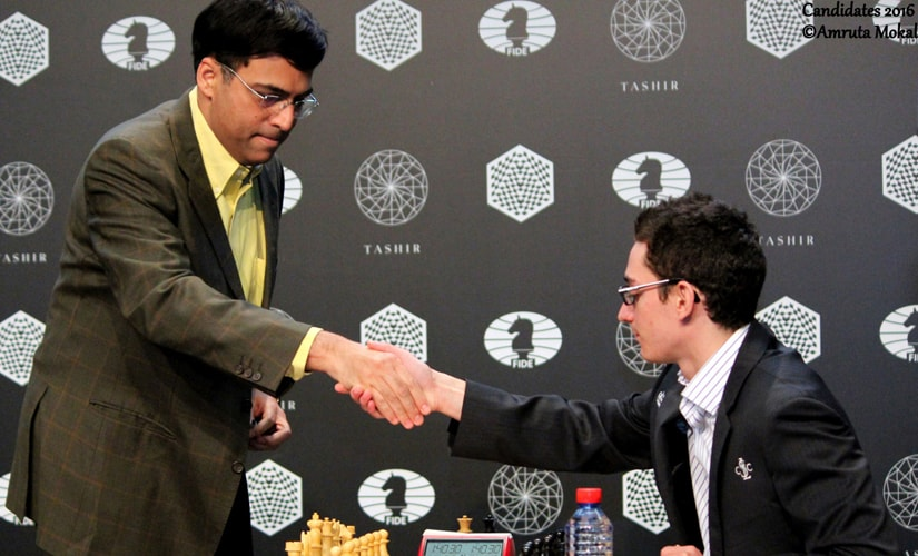 Viswanathan Anand greets Fabiano Caruana before the start of their Round 3 match at the Central Telegraph Building in Moscow on Sunday. Amruta Mokal