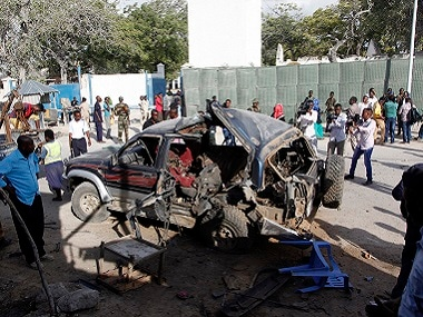 The wreckage of a car used for a suicide bombing sits outside a police academy in Mogadishu. AP