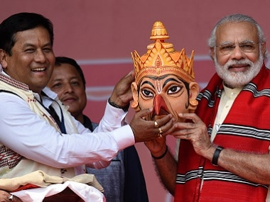 Prime Minister Narendra Modi poses with BJP's Sarbananda Sonowal as he is given a traditional Assamese mask at an election rally at Majuli Island. AFP