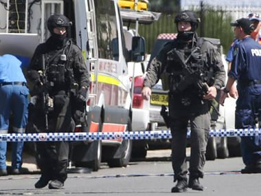 Police Tactical Group officers walk on a cordoned off street of an industrial section of Ingleburn, in suburban Sydney, Monday, March 7, 2016 as police respond to a shooting. AP