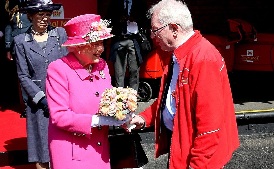 Queen Elizabeth II meets Britain's longest serving postman Bob Hartley. Reuters