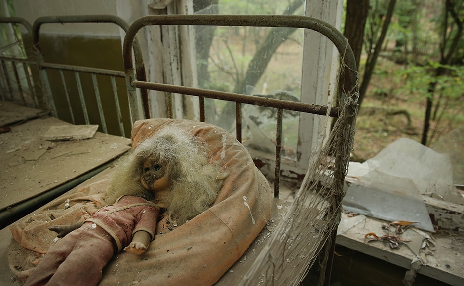 CHORNOBYL, UKRAINE - SEPTEMBER 29: A doll lies among children's beds standing in the abandoned kindergarten of Kopachi village located inside the Chernobyl Exclusion Zone on September 29, 2015 near Chornobyl, Ukraine. Kopachi, a village that before 1986 had a population of 1,114, lies only a few kilometers south of the former Chernobyl nuclear power plant, where in 1986 workers inadvertantly caused reactor number four to explode, creating the worst nuclear accident in history. Radiation fallout was so high that authorities bulldozed and buried all of Kopachi's structures except for the kindergarten. Today the Kopachi site, which lies in the inner exclusion zone around Chernobyl where hot spots of persistently high levels of radiation make the area uninhabitable for thousands of years to come, is still contaminated with plutonium, cesium-137 and strontium-90. (Photo by Sean Gallup/Getty Images)