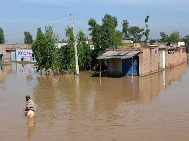 A Pakistani resident walks through a flooded area following heavy rain on the outskirts of Peshawar on Monday. AFP