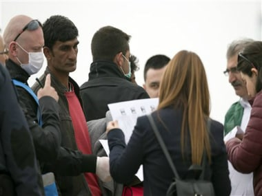A Frontex staff member and Turkish Interior Ministry employees check documents of a Pakistani migrant, second from left, before getting on a ferry for Turkey in the port of Mytilini of the Greek island of Lesbos, Friday, April 8, 2016. AP