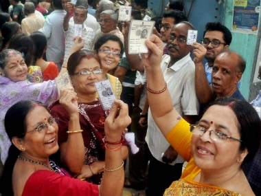 Voters shows their voter cards as they stand in queues to cast their votes in Kolkata on Saturday. PTI