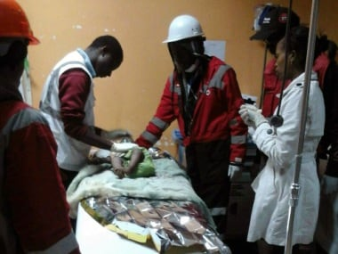 """A handout picture taken and released on May 3, 2016 by Kenya Red Cross shows Kenyan Red Cross staff with a 18-month-old toddler rescued alive from the rubble of a six-storey building on May 2, four days after the block collapsed killing 23 people. The Red Cross said the little girl was found """"in a bucket wrapped in a blanket"""" and was dehydrated but without visible physical injuries. She had been there for 80 hours since the building, which was home to 150 families crammed into single rooms, collapsed April 29. / AFP PHOTO / KENYA RED CROSS / BONNY ODHIAMBO / RESTRICTED TO EDITORIAL USE - MANDATORY CREDIT """"AFP PHOTO / KENYA RED CROSS/ BONNY ODHIAMBO- NO MARKETING NO ADVERTISING CAMPAIGNS - DISTRIBUTED AS A SERVICE TO CLIENTS"""