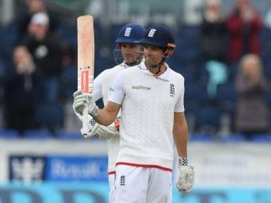 England batsman Alastair Cook raises his bat after reaching 10,000 test runs. Getty