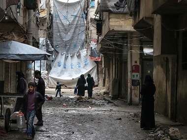 Civilians walk through a street in Aleppo with large tarps hung in between buildings. Komsomolskaya Pravda via AP