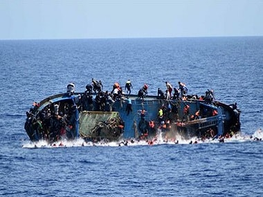 People jump off a boat moments before it overturns off the Libyan coast, Wednesday, May 25, 2016. On Friday, the Italian navy says it has saved 135 migrants and recovered 45 bodies. AP.