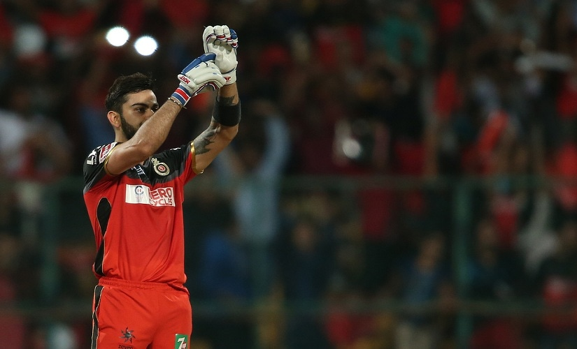 RCB captain Virat Kohli celebrates his century by pointing to his injured hand with stitches. BCCI