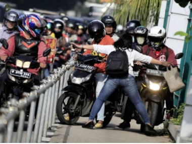Alfini Lestari was pictured with her arms outstretched as she physically blocked a horde of motorbikes from riding down the pavement during rush hour this week. AFP