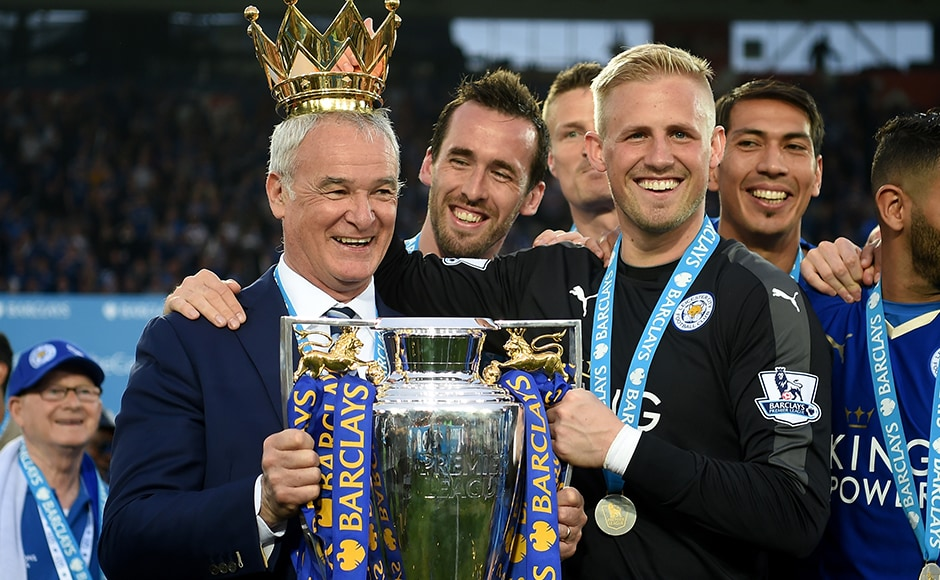 Claudio Ranieri poses with the Premier League Trophy while Kasper Schmeichel puts the crown on the head of the manager as players and staffs celebrate the season champions after the Barclays Premier League match between Leicester City and Everton at The King Power Stadium on May 7, 2016 in Leicester, United Kingdom. Getty